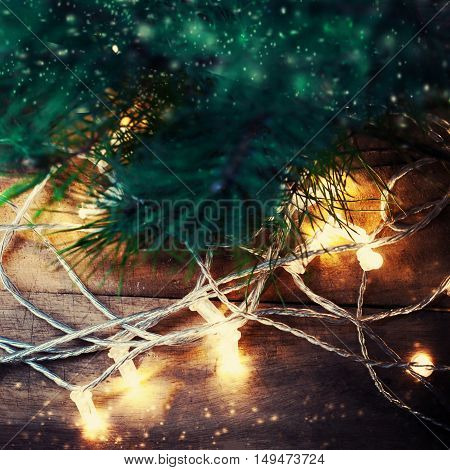 Christmas card with fir tree branch over wooden background with lighting festive garland.