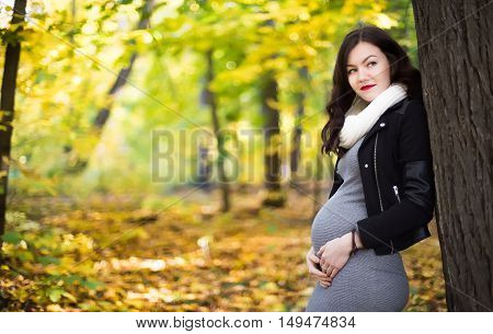 young pregnant woman leaning against a tree in autumn forest