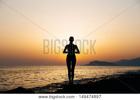 Young healthy woman practicing yoga on the beach at sunset. Copy space text