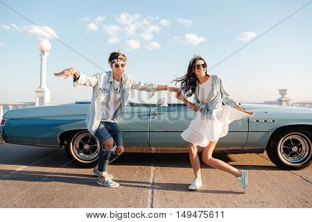 Happy young couple dancing outdoors in summer