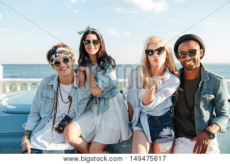 Portrait of happy young friends standing and sending kiss outdoors