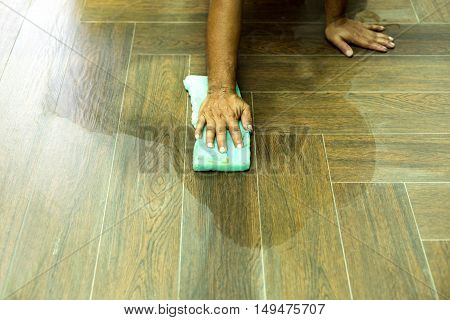 Worker cleaning floor tile after grouting tiles with sponge in construction site