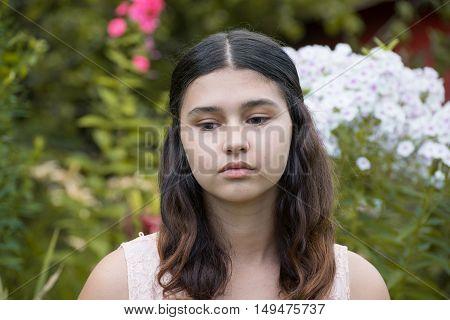 A teen girl against a white phlox