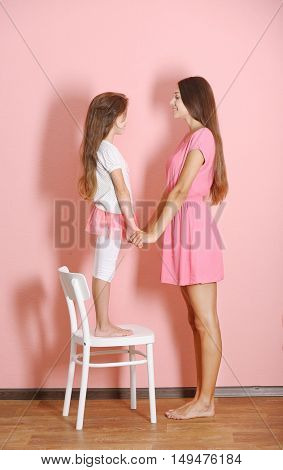 Cute girl with mother on pink wall background