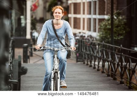 Woman Cycling In An Old Town