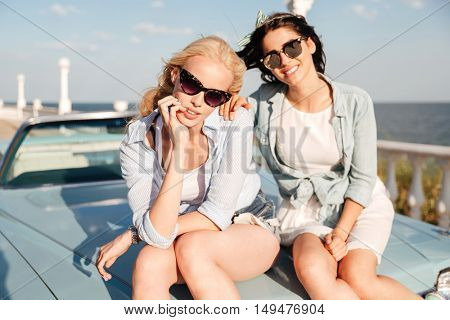 Two beautiful young women sitting on the car hood together