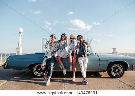 Multiethnic group of cheerful young people standing near vintage cbriolet