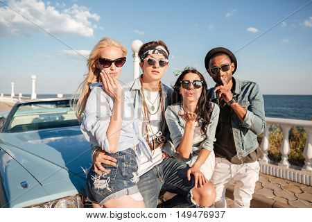 Multiethnic group of happy young people standing and sendng kisses near vintage cabriolet in summer