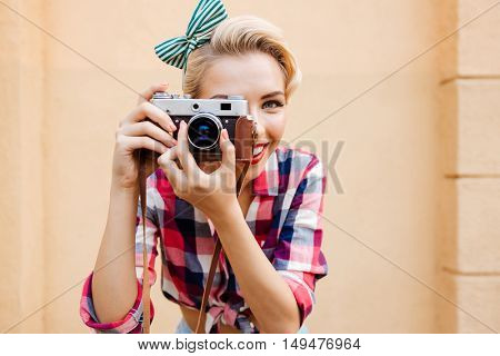 Close up portrait of a smiling attractive young woman taking photos using old camera over pink background