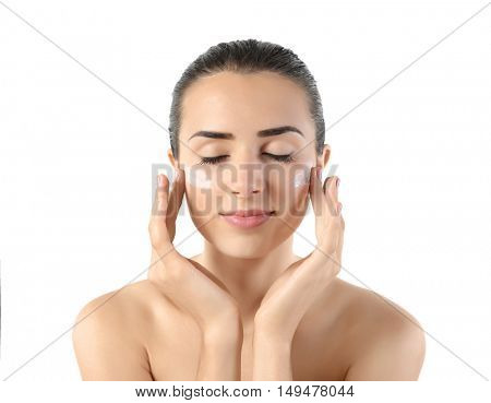 Young woman applying facial cream on white background