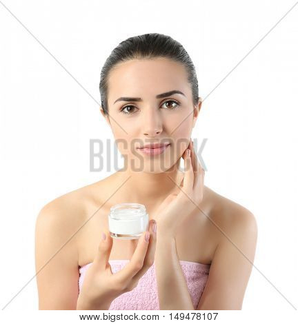 Beautiful young woman with natural makeup holding facial cream on white background