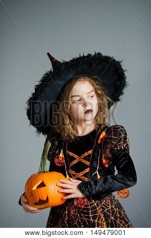 Halloween. Girl portray evil sorceress.She is wearing black-and-orange dress and hat. From under his hat sticking disheveled hair. Girl has an evil expression. In hands at her pumpkin - Jack o lantern