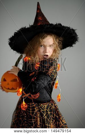 Halloween. Girl portray evil sorceress. She is wearing a black-and-orange dress and hat. From under his hat sticking disheveled hair. Girl has an evil expression. In hands at her pumpkin - Jack o lantern