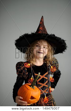Halloween. Girl portray evil sorceress. She is wearing black-and-orange dress and hat.From under his hat sticking disheveled hair. Girl has an evil expression. In hands at her pumpkin - Jack o lantern