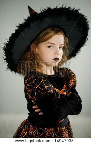 Preparation for Halloween. Beautiful girl 8-9 years shows the evil witch. She is dressed in black and orange dress and a big hat. On the face of the appropriate makeup. Children adore Halloween.