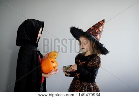 Boy and girl in suits for Halloween. They in image powers of darkness. Girl - evil fairy boy - warlock. Girl holds sweets in hands. Boy holds pumpkin with a candle inside - Halloween symbol. Boo