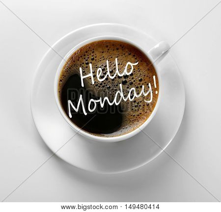 Text HELLO MONDAY and cup of aromatic coffee on white background, closeup