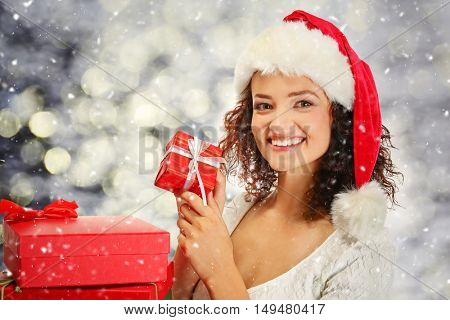 Beautiful happy woman with Christmas gifts on blurred lights background. Christmas holiday concept.