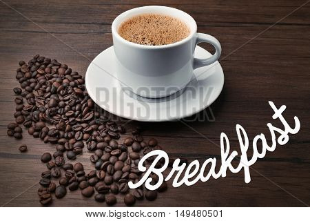 Word BREAKFAST and cup of aromatic coffee on wooden background
