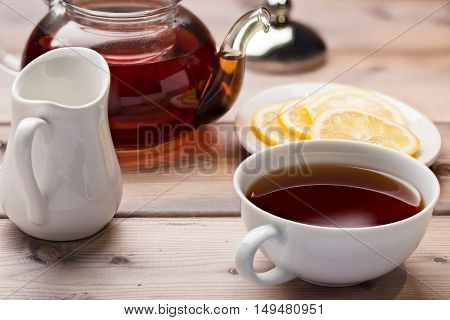 Glass teapot and teacup on wooden background