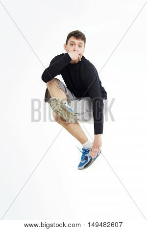Hip hop dancer performing isolated over white background. Hip hop performer is standing in hip hop jumping pose. Jump of break-dancer.