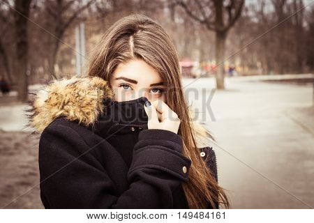 Outdoor portrait of a teenage girl covering her face with a black coat.