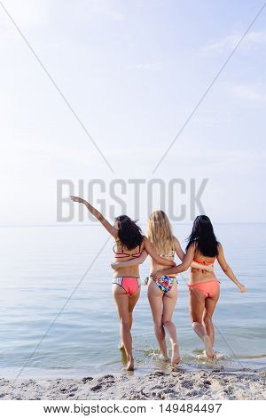 Group of young pretty girls having fun on the beach. Joyful friends. Holiday concept. Copyspace text.