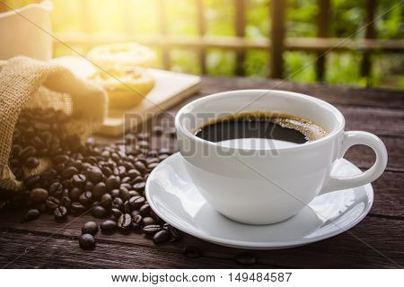 Cup of coffee beans on the table with light sunlight at dawn / concept vintage.