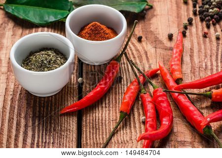 Different spices in bowls and scattered on wooden table