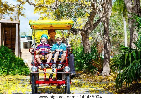 Yound dad and two little kid boys biking on bicycle in zoo. Family with active leisure and watching animals. Father and sons having fun together.