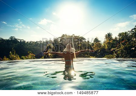 Infinity Pool At Luxurious Exotic Island. Portrait Of Girl Wearing Hat Enjoying The Sun At Pool