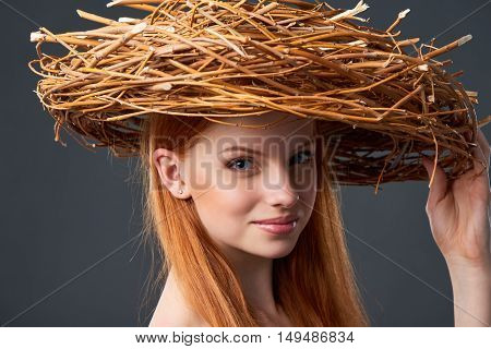 Closeup of smiling beautiful woman in natural wreath of wicker