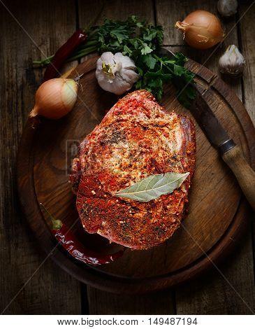 raw piece of pork, onion, pepper, garlic, fresh herbs on the wooden background