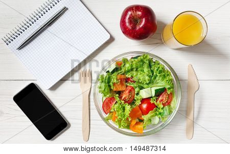 Healthy business lunch in office, top view of vegetable salad on white wooden desk with wood cutlery. Salad bowl, apple, orange juice, mobile phone and notepad with pen flat lay. Snack at break time