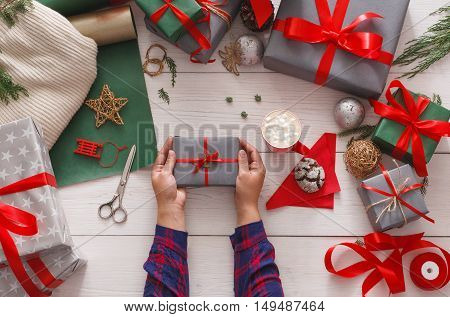 Creative diy hobby. Making modern handmade christmas present, boxes in stylish paper with satin red ribbon. Top view of hands on messy white wood table with fir tree branches, decoration of gift.