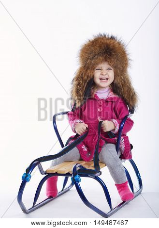 little beautiful girl with sled on white background