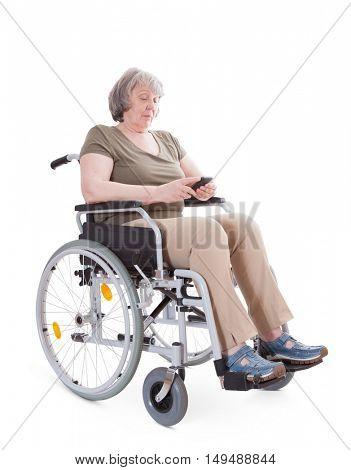 Senior sitting in wheelchair using smart phone. All on white background.
