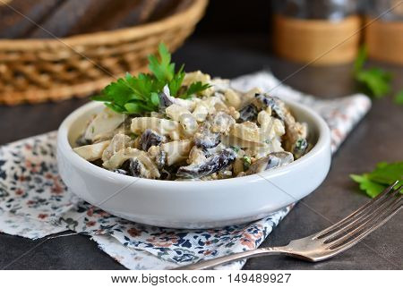 Holiday salad with mushrooms, vegetables and cream sauce on a black background