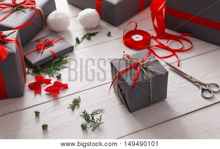 Creative diy hobby. Handmade tools for making modern christmas present, boxes in stylish gray paper with red ribbon. View of messy white wooden table with fir tree branches, decoration of gift.