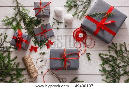 Creative diy hobby. Handmade tools for making modern christmas present, boxes in stylish gray paper with red ribbon. Top view of messy white wooden table with fir tree branches, decoration of gift.