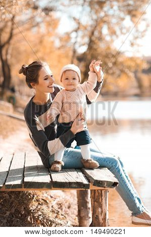 Smiling woman holding baby girl wearing knitted casual clothes sitting in autumn park. Happiness.