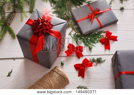 Creative diy hobby. Handmade tools for making modern christmas present, boxes in stylish gray paper with red satin ribbon. Messy white wooden table closeup with fir tree branches, decoration of gift.