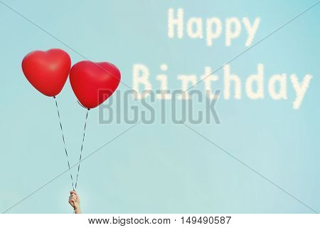 Happy Birthday text and love heart balloons on sky background