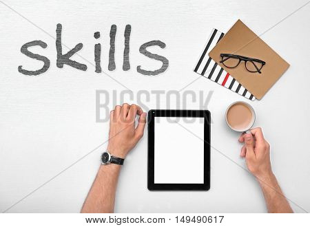 Skills. Man working with tablet, top view