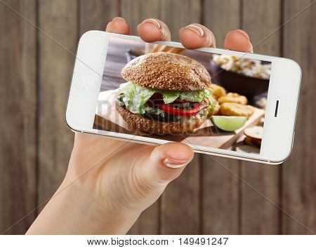 Female hand holding smartphone on blurred wooden background. Photo of food on smartphone screen.