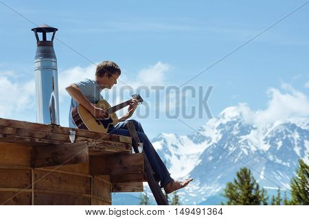 Man plays on guitar on the roof of house on background of mountains
