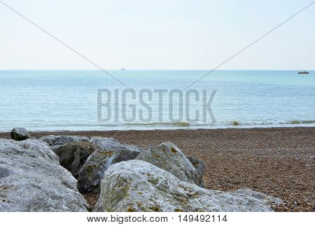 Rocks and shingle beach with boats at sea. Lancing West Sussex England