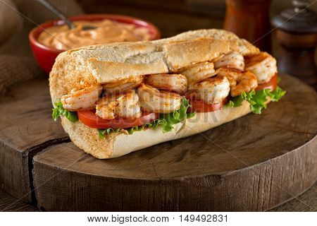 A delicious home made grilled shrimp Po Boy sandwich on baguette dressed with lettuce tomato and remoulade.