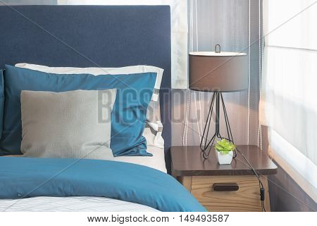 Modern Blue Color Tone Bedroom With Lamp And Vase Of Plant