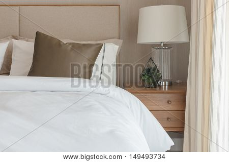 Brown Pillow On White Modern Bed With Lamp On Table Side